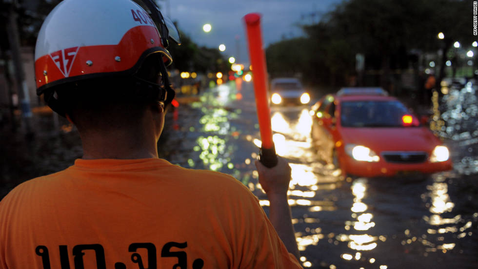 A Thai police officer directs traffic as cars pass through flooded streets on Friday. Residents have begun leaving Bangkok to escape the rising waters.