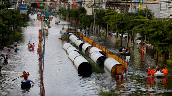 People paddle and walk through a flooded neighborhood near the Chao Praya River.