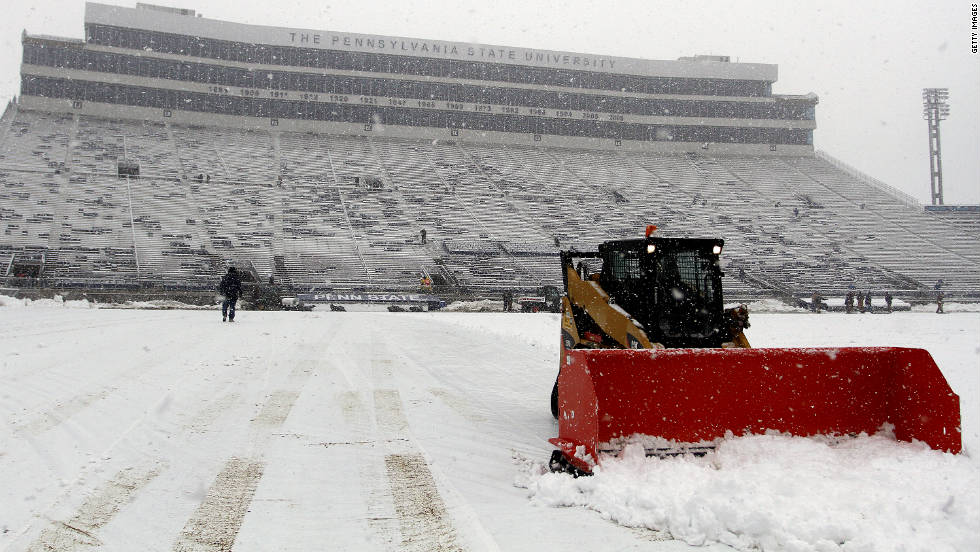 A snowplow removes snow from Penn State University's Beaver Stadium on Saturday. The early season snowstorm was the result of unseasonably cold air mixing with a storm system on the East Coast.