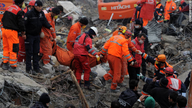 Rescue workers carry the body of a victim in Ercis, Turkey, on Thursday, after an earthquake shook the area.