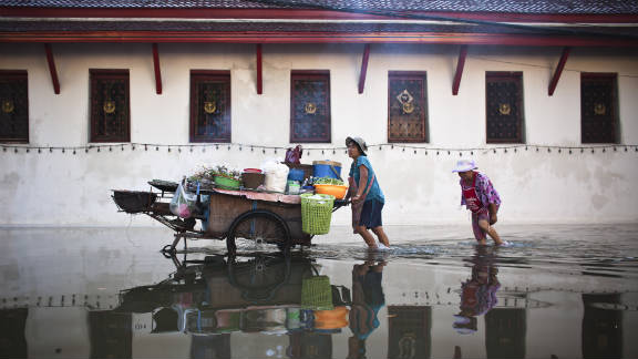 People commute along a flooded street near the Chao Phraya River on Sunday in Bangkok.