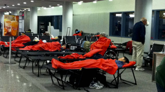JetBlue passengers stranded in Hartford, Connecticut, sleep on floors and cots at the airport. They had to line up to get new seats on their diverted flights.