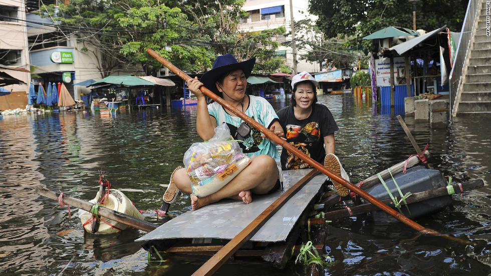 Bangkok residents paddle a makeshift boat through floodwaters on Sunday, October 30. Thai officials warned residents in the capital to be vigilant and expect disruptions with electricity and tap water as Thailand battles its worst flooding in decades.