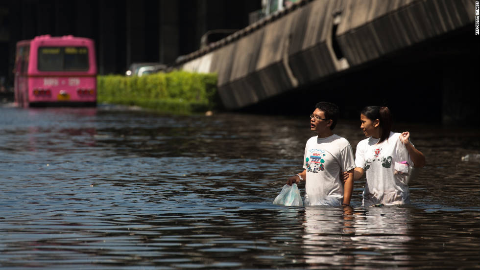 Residents  commute along a flooded street on Sunday.