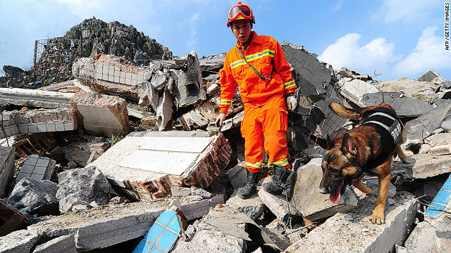 A firefighter in Fuquan searches through debris after two trucks carrying explosives detonated.