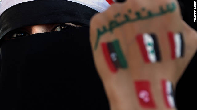 A Yemeni woman shows her fist with flags of Arab countries who took part in the Arab Spring.