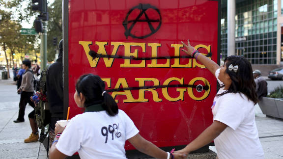 Protesters run by a defaced Wells Fargo bank sign during Occupy Oakland
