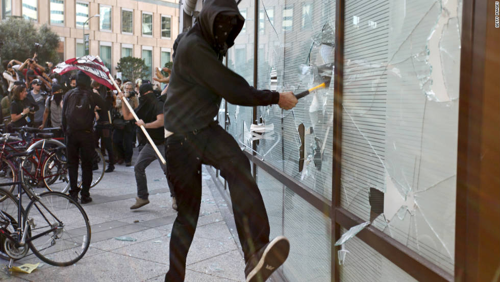 A masked protester smashes a window at a Wells Fargo bank during the citywide general strike Wednesday. Police said a small group vandalized some Oakland businesses, including banks and a grocery store.