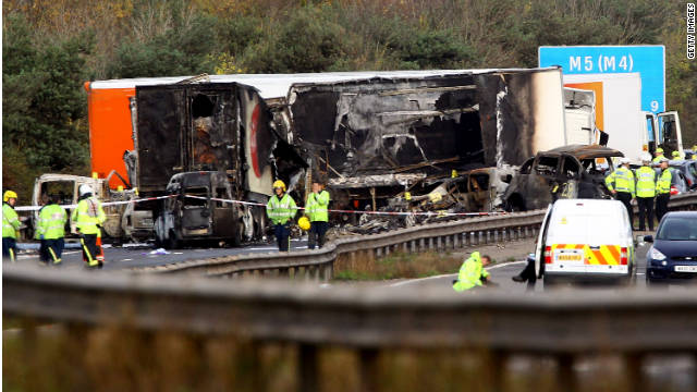 Workers attend the scene of a multivehicle crash on the M5 motorway on Saturday in Taunton, England.
