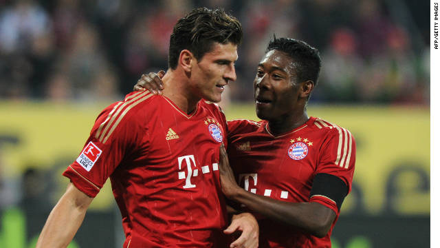 Mario Gomez (left) celebrates scoring his 20th goal of the season as Bayern won 2-1 at  Augsburg.