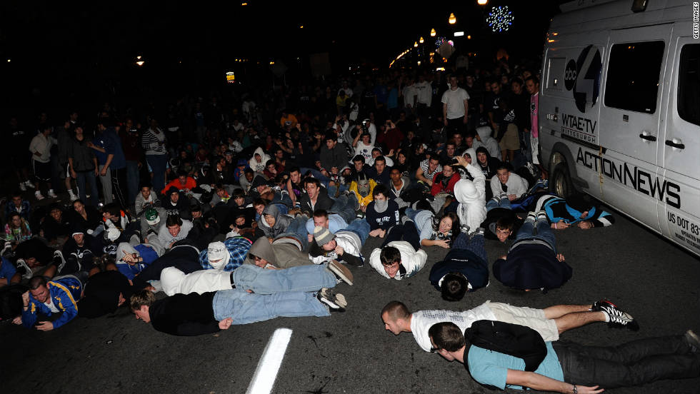 Police try to control students in the street after what started as an apparent celebration of Paterno turned raucous.