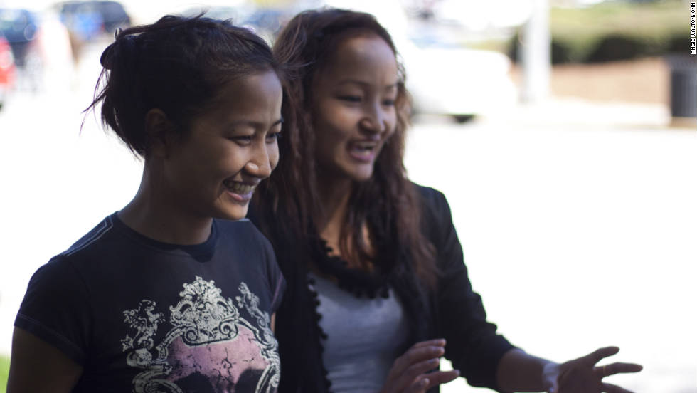 Rita, left, laughs with her older sister Melody as they walk back to class. Rita and Melody have been in the United States for one year.