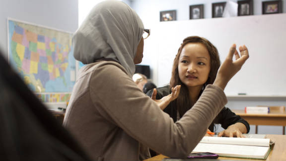 Melody, right, works with a tutor in reading class as she learns English. Melody says reading is her favorite subject.