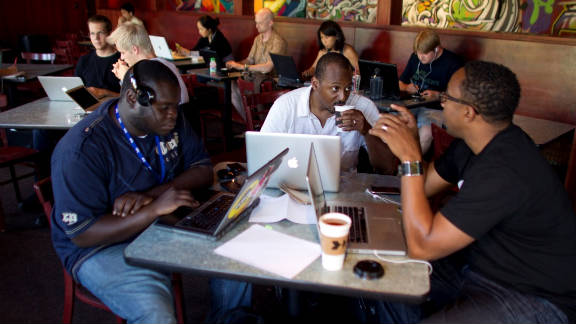 NewMe co-founder Wayne Sutton, center, works on his laptop at a coffee shop with fellow entrepeneurs.