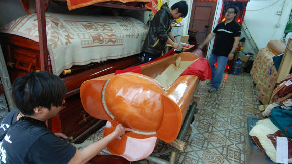 Workers in a funeral parlor in Hung Hom put the finishing touches on a casket