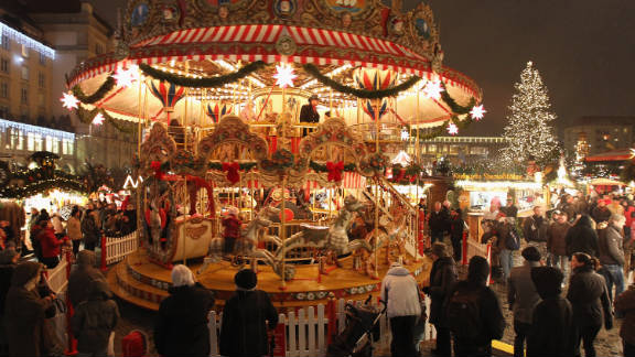 Visitors watch an ornate merry-go-round at the illuminated Dresdner Striezelmarkt Christmas market on November 26, 2010 in Dresden, Germany. The Striezelmarkt claims to be Germany