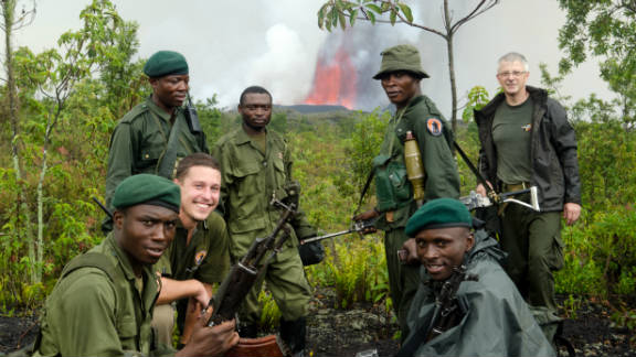 Some of the Virunga National Park team pose in front of the erupting volcano during a trek to the eruption site soon after it started on November 6.