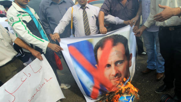 Protesters burn portraits of Syrian President Bashar al-Assad outside the Arab League headquarters in Cairo on November 12.