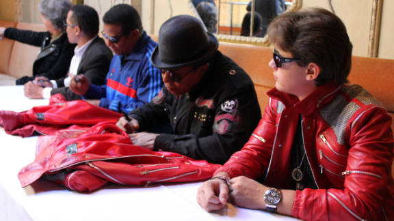 """Prince Jackson with uncles Jackie, Marlon, and Tito Jackson, signing special edition """"Beat It"""" jackets."""