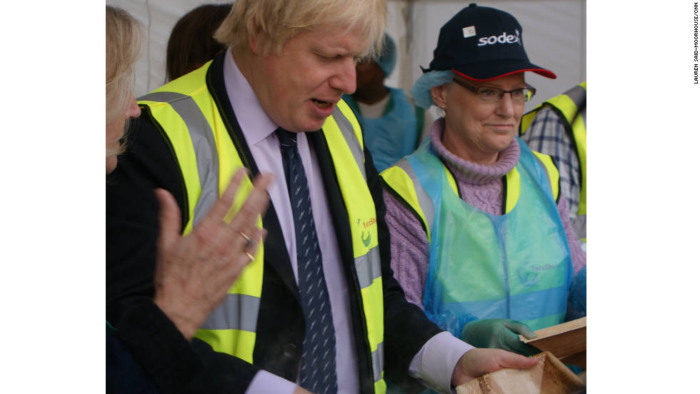 "Mayor of London Boris Johnson dishing up some food at the event. Many of the ingredients are considered waste by restaurants, businesses and retailers. Speaking at the event, Johnson spoke of the practice of throwing away misshapen ingredients saying: ""Don't discriminate against mutant vegetables."""