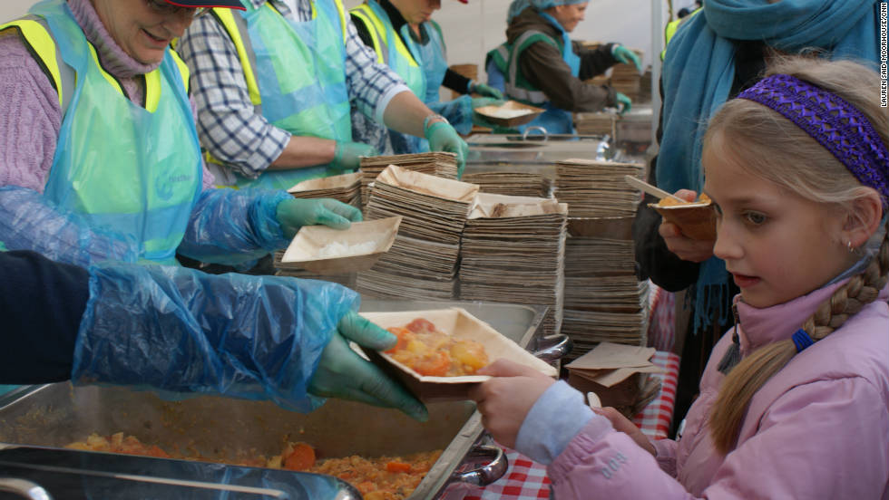 A young girl receieves her free waste curry made from potatoes, carrots, corn, cauliflower amongst other ingredients. Organizers says that an estimated 20-40% of UK fruit and vegetables are rejected even before they reach the shops as they don't match supermarkets' strict cosmetic standards.
