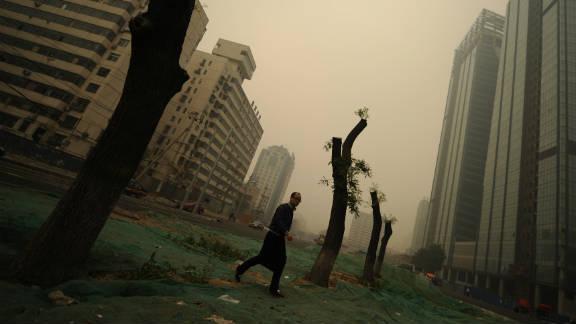 A man walks through heavy pollution on a street in Beijing on November 2011.