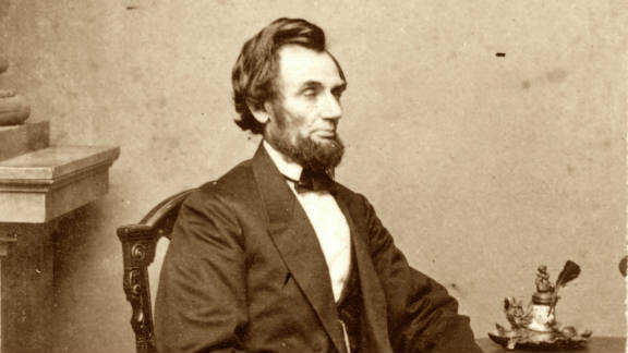 President Abraham Lincoln poses for a portrait next to a table in 1865.