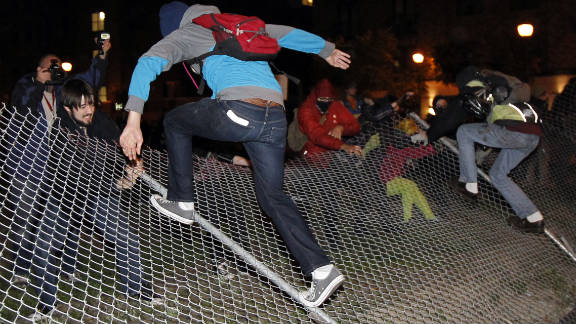 Demonstrators pull down a chain-link fence Saturday in Oakland, California. Protesters took over a vacant lot in downtown Oakland, claiming it as their new encampment.