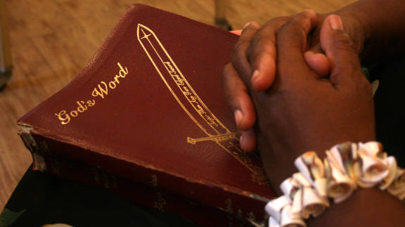 """Pastor Byrth lays her Bible on her lap before a meeting at Bibleway Holiness Church. """"I never try to push Gospel on people because God is a gentleman, he never  pushes himself on us,"""" she says. """"He always gives us a choice."""""""