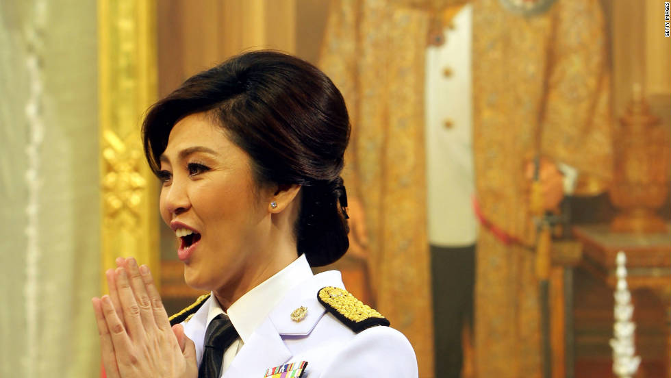 Yingluck Shinawatra is Thailand's first female Prime Minister and sister of former Thai leader, Thaksin Shinawatra. Here she is waiing which is a traditional Thai way of greeting someone near a portrait of Thailand's King Bhumibol Adulyadej shortly after taking office.