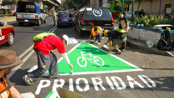 """A group of urban activists paint an unauthorized  """"wikilane"""" cycle path in the middle of Mexico City."""