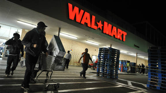 Shoppers wheel their purchases out of a Wal-Mart store in Los Angeles, California November 27, 2009.