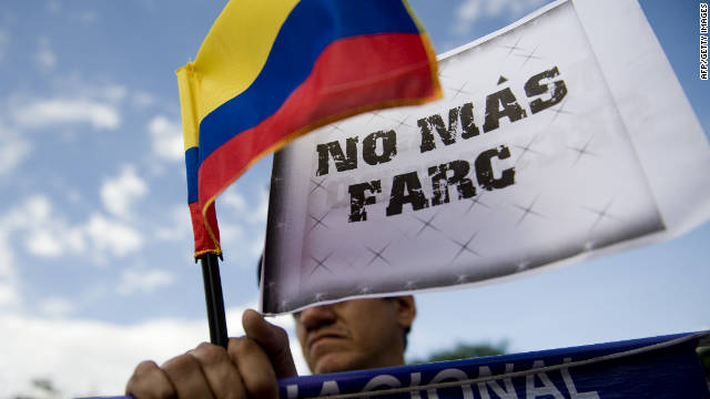 "A man holds a Colombian flag with a sign that reads ""No more FARC"" on Wednesday, November 23, in Cali, Colombia."