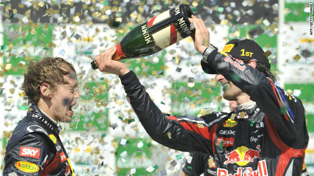 Brazil winner Mark Webber pours champagne on teammate and champion Sebastian Vettel.