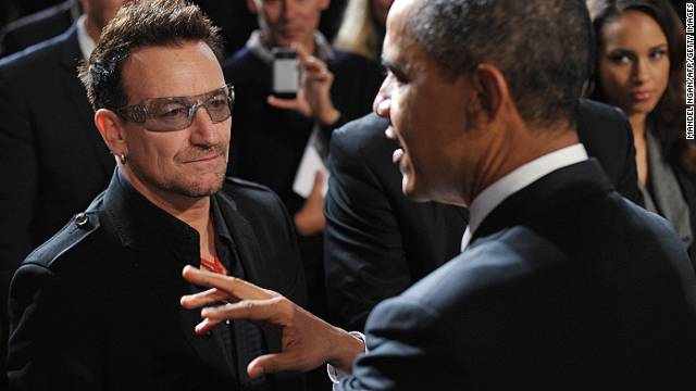 President Obama announces the removal of the U.S. HIV travel ban as singer Bono looks on.