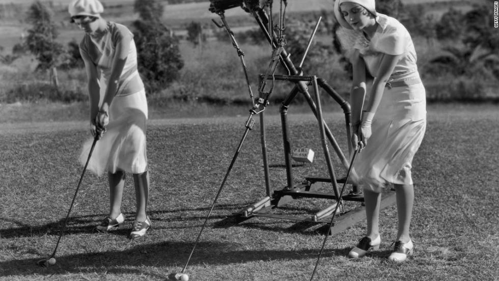 An early prototype robot was used to assist two women golfers with their swings in this 1925 picture.