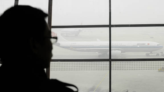 A  traveler at Beijing International Airport looks out at planes stranded due to thick fog, which caused widespread travel disruption