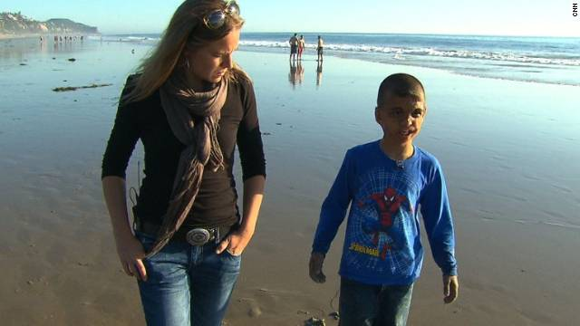 Youssif walks along a California beach with CNN's Arwa Damon, who first told the boy's story in 2007.
