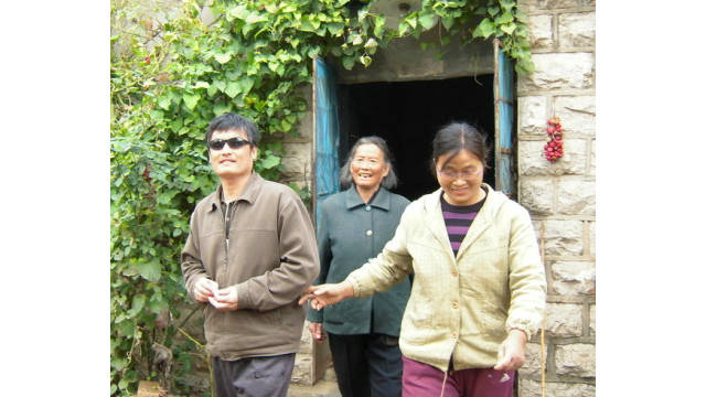Chen, his wife and his mother smile and wave goodbye to an unseen guest outside their house.