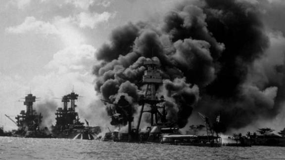 The USS Arizona burns in Pearl Harbor on December 7, 1941. To the left are the USS Tennessee and the USS West Virginia.