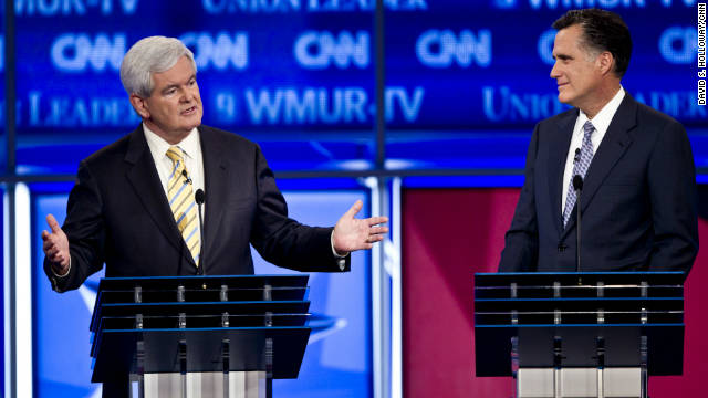 Former Speaker of the House Newt Gingrich speaks and former Massachusetts Governor Mitt Romney listens at the CNN GOP Debate at Saint Anselm College in Manchester, New Hampshire on Monday, June 13, 2011.
