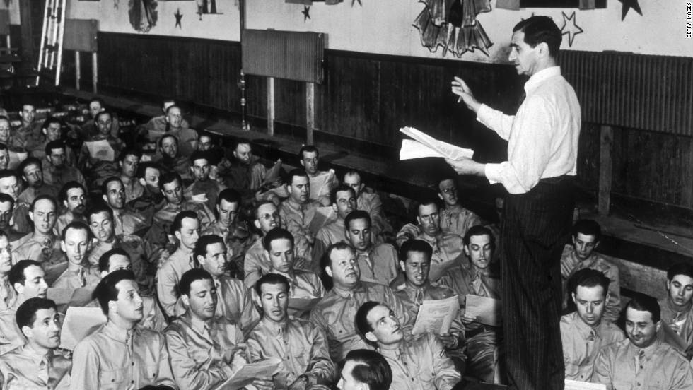 "Composer Irving Berlin leads a group of servicemen at Camp Upton in Long Island, New York, in 1942. Berlin wrote ""God Bless America."""
