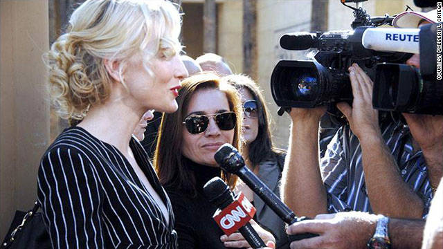 Martinez stands behind Cate Blanchett and facilitates questions and answers from the media.