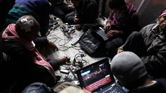 Egyptian anti-government bloggers work on their laptops from Tahrir Square during last year