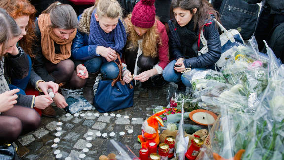 People leave tributes at the site of Tuesday