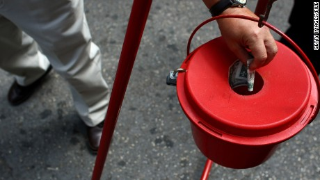 Donors put money in red Salvation Army kettle.