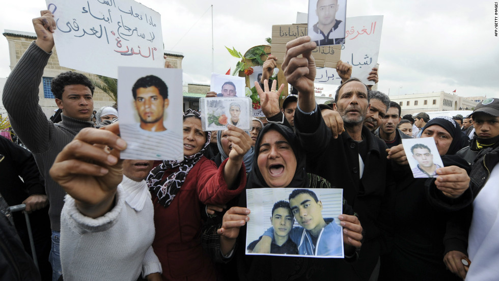 Tunisians show pictures of relatives who died during the revolution at a rally on March 19, 2011 in Tunis.