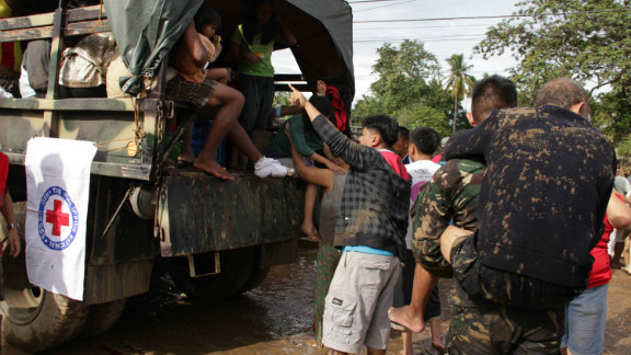 Military personnel help evacuate residents from a village in Iligan City on Saturday, December 17, after Tropical Storm Washi struck in the southern Philippines. Flash floods and mudslides from the storm killed hundreds.