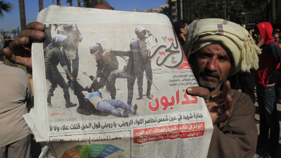 A newspaper photo shows Egyptian security forces beating a female demonstrator during clashes in Cairo on Sunday.