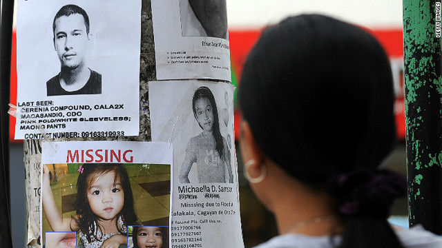 A woman looks at posters of missing persons in Cagayan de Oro City in Mindanao on December 22, 2011.